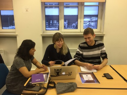 Three ESRs working as a group around a table during the workshop